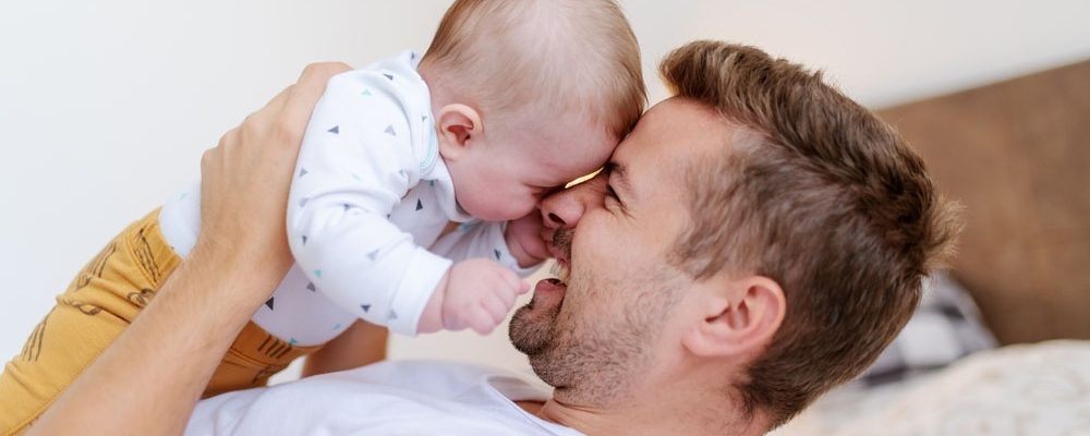 Handsome young dad lying in bed in bedroom and lifting his loving laughing baby boy six months old. Unconditional love concept.